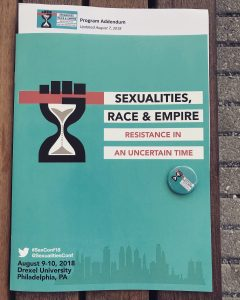 Photo of the conference program, teal background with logo which is a hand with an hourglass as the wrist and fist